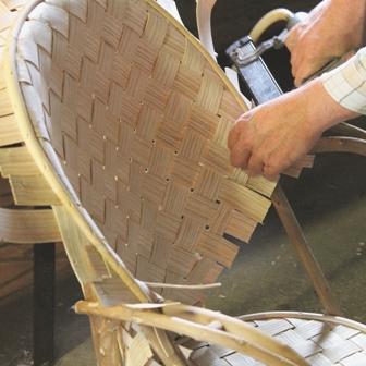 fabrication de fauteuils en châtaignier, pose du jonc sur le bord